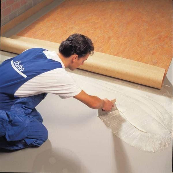 нанесение клея на бетонный пол